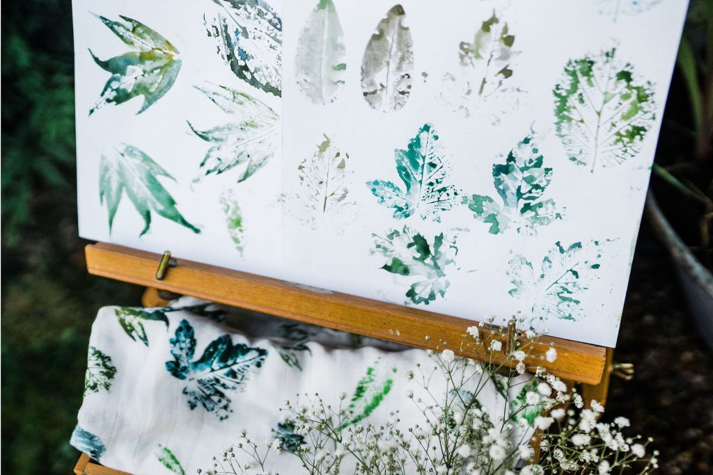 Easel holding painting of leaves with muslin printed in the same design underneath