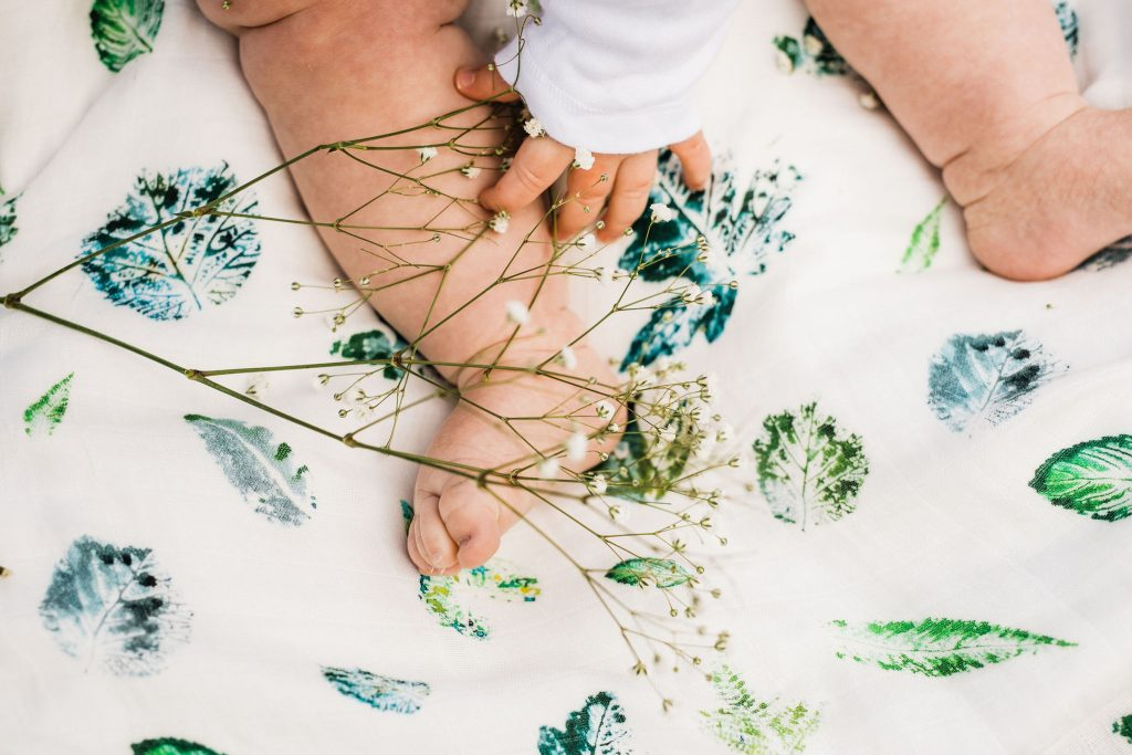 Babys hand and feet clutching flowers on top of leaf print muslin